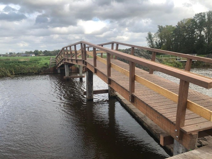Een nieuw brugdek in aanbouw. De brug is bruin. En achter de brug zie je een groen landschap.